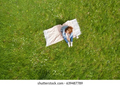Solitary young woman relaxing on a rug on green spring grass sitting with her knees up viewed from high overhead with copy space