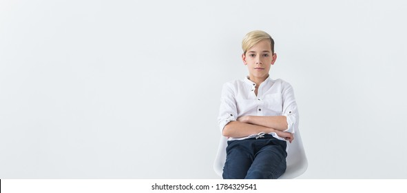 Solitude, loneliness and boredom concept - Bored teen student sitting in a school chair isolated on white background