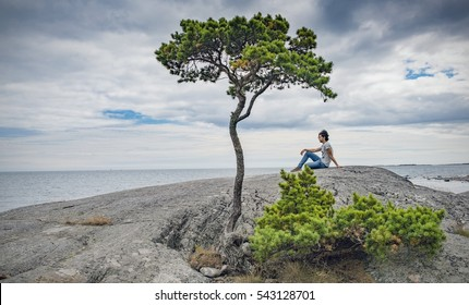 Solitude and Loneliness expressed by a young man, the sea, and a lonely tree