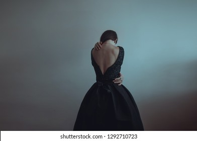 Solitude. Lonely girl stands near the gray wall. Loneliness, sadness, depression, disappointment. Woman in vintage black dress. Girl is afraid and hugs herself. Dramatic picture. Pain.
