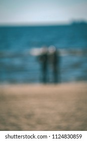 Solitude. Lonely and pensive man on the beach at the sea. A man sitting leaning on her legs. He is thinking. - vintage retro look