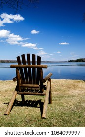 solitude on the shore of a calm lake in MInnesota with a lone chair and heavenly skies