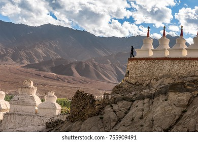 Solitude at Shey Palace . The lone women standing at the edge of the Stupas of the Monastery gave a added a essence of solitude . Seemed she might be pondering over the vastness of the nature