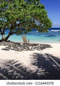 Solitude - a single deckchair for relaxation in the shade on a beautiful tropical sandy beach at Lefaga, Matautu, Upolu Island, Western Samoa, South Pacific - portrait orientation