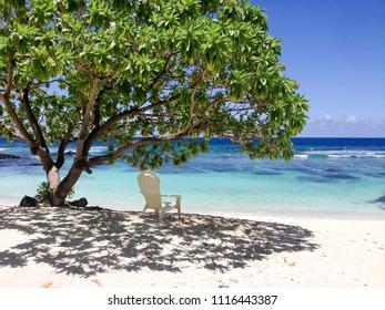 Solitude - a single deckchair for relaxation in the shade on a beautiful tropical sandy beach at Lefaga, Matautu, Upolu Island, Western Samoa, South Pacific - landscape orientation