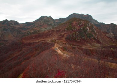 Solitude and tranquility. Little house in the mountains: autumn landscape at the top of the mountain, forest and red trees, beautiful background, bright colors of autumn, secluded life in the mountain