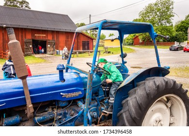 SOLLENTUNA, SWEDEN - JUNE 17, 2016: Family day rural scene with a litte boy in a blue tractor and other families in the background at a red barn in Sollentuna Sweden June 17, 2016.