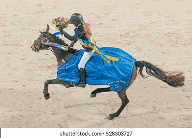 SOLNA, SWEDEN - NOV 26, 2016: Lap of honour with Mathilda Bohlin at the prize cermony with Prince Carl Philip in the ponny jumping at the Sweden International Horse Show in Friends arena.
