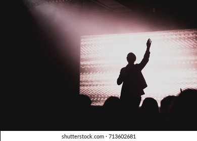 Solo artist raising hands at contemporary church conference silhouette against LED screen on stage