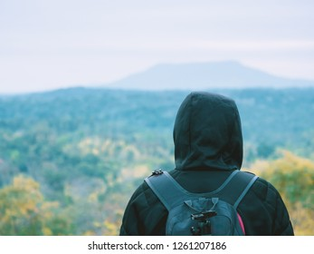 solo backpack and camping concept from backside of black hair man in warm hoodie sweatshirt with his bag solo travel, relax, happy  and see to forest and mountain in morning after sunrise
