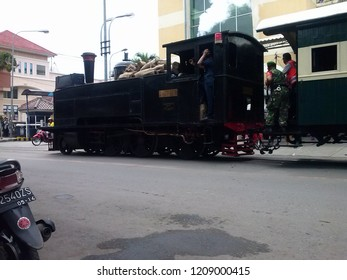 Solo, Central Java, Indonesia - December 28, 2014 : An old steam engine train passed the city road to attract tourist in Solo, Indonesia.
