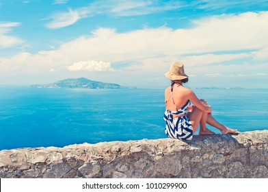 solo female traveller wearing hat sitting with her back to camera on old wall on top of Monte Solaro on Capri island on sunny summer day, Italy