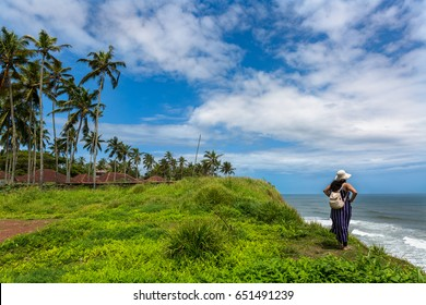 Solo girl traveler standing on a cliff at a beach town called Varkala in Kerala, India. Blue skies, white clouds, tropical, green grass, landscape, beautiful travel wallpaper / advertisement