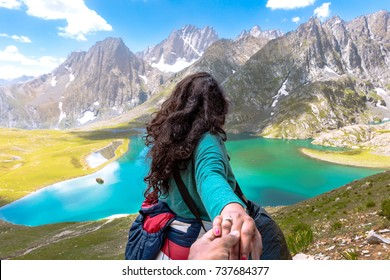 Solo girl traveling in the mountains of Kashmir, India. Great lakes of kashmir. red green and blue colors of  Himalayas. Wanderlust Nature image. Blue skies and Turquoise lake. Valleys and meadows .