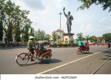 Solo Indonesia - Jul 31, 2016 : Tricycle pass-by one of Solo City statue landmark pictured on Jul 31, 2016. Solo is famous for its traditional home based Batik industry in Central Java Indonesia.