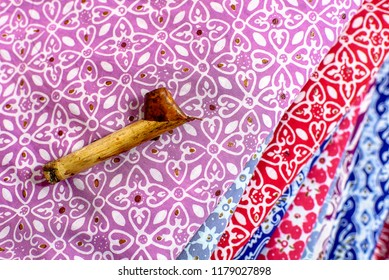 SOLO INDONESIA, SEPTEMBER 14 2018 : Traditional canting for making Batik Tulis in Surakarta with background colorful Fabric
