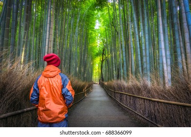 Solo Male Traveler standing from behind at the green bamboo forest in Arashiyama, Kyoto, Japan, wearing winter orange and red clothes looking at the long path.