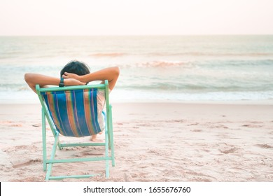 solo man travel relax and sit on beach chair see to beach and sunset background on summer season