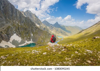 Solo person in the mountains of Kashmir, India. Great lakes of kashmir. red green and blue colors of  Himalayas. Wanderlust Nature image. Landscape,Blue skies and Turquoise lake. Valleys and meadows .