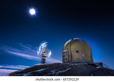 Solo Person spinning light outside of dome building in moonlight