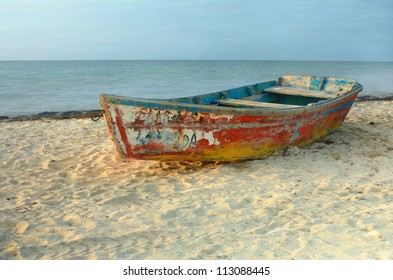 Solo rowboat with peeling paint resting on sandy beach in Progreso, Yucatan, Mexico