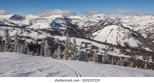 Solo up ski track looking west of Jackson hole with wind sculpted snow.