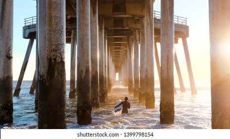 A solo surfer catching sunset waves under the Huntington Beach Pier in California.