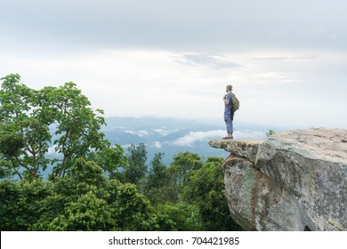 Solo traveler adventurer standing on the edge of a rock cliff watching a natural landscape of forest and jungle with mist and fog over the mountains