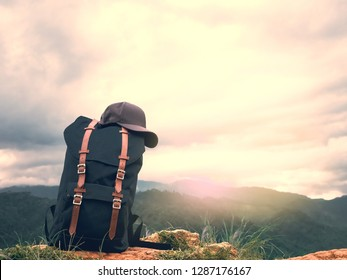 solo traveler hike and camping in summer concept from blue backpack with brown cap put on floor with tropical forest and beautiful sky background