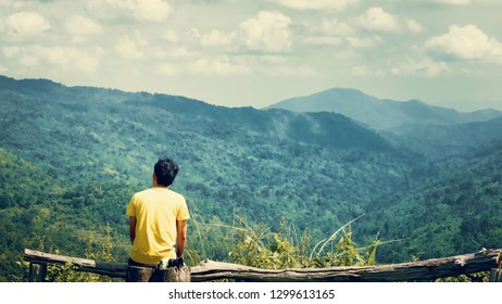 solo traveler hike and camping in summer concept from backside of asian man during breathe the fresh air and see mountain view in tropical forest background
