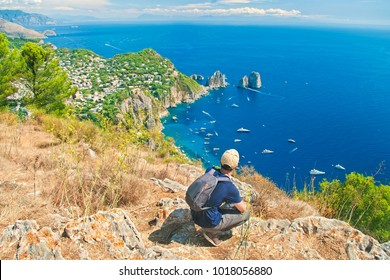solo traveler resting after climbing up mount Solaro overlooking famous faraglioni rocks on sunny summer day, Capri, Italy