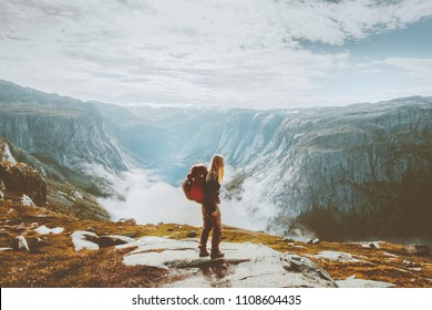 Solo traveling girl hiking with backpack in mountains adventure journey lifestyle vacations weekend getaway in Norway