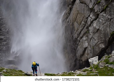 A solo trekker is approaching to the roaring Vasudhara falls surrounded by rocky brown mountains & clouds situated near Mana (last indian village). Monsoon trek taken in August in Uttarakhand India.