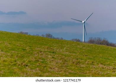Solo wind turbine on a hillside against overcast sky
