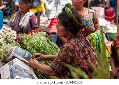 SOLOLA, GUATEMALA- MAY 10: An unidentified woman sells flowers at traditional weekly market in Solola), Guatemala on 10 May 2013.
