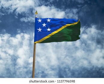 Solomon Islands flag Silk waving flag of Solomon Islands  made transparent fabric with wooden flagpole gold spear on background blue sky white smoke clouds real photo Countries world 3d illustration