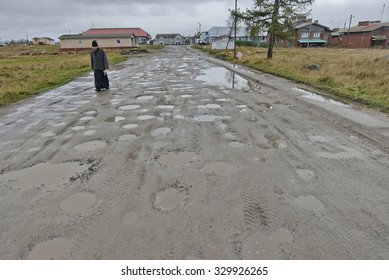SOLOVETSKY ISLANDS, RUSSIA - SEPTEMBER 28: Unidentified  Orthodox monk goes along muddy street on Solovetsky Island, Russia, September 28, 2012. There is conflict between monks and secular authority.