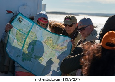 SOLOVKI, REPUBLIC OF KARELIA, RUSSIA - JUNE 24, 2018: Tourists on the ship, at sea, are developing a route on the map of the Solovetsky Islands. White Sea, Arkhangelsk Region, Russia