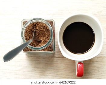 soluble instant coffee powder with silver tea spoon in transparent glass jar and brewed black coffee in white ceramic cup with red handle on wood plank table in coffee shop, flat lay close up top view