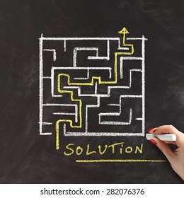 Solution or problem solving concept with a female hand drawing a maze or labyrinth on a blackboard with a yellow arrow marking the route through the puzzle