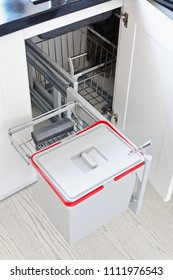 A solution for storing the trash can in the kitchen cupboard under the sink. Corner unit with a pull-out shelf for the trash can.