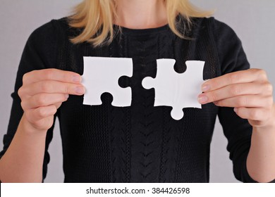 Solutions, partnership concept. Woman holding two pieces of a blank puzzle