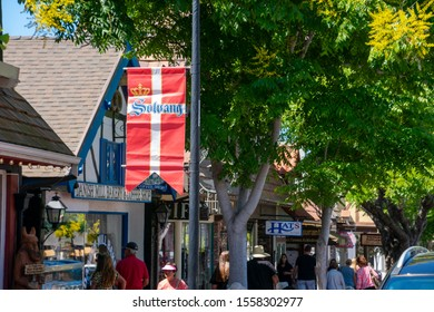 Solvang, California/USA - September 12, 2019: People walking a shopping street in the town of Solvang; red and white Danish flag with crown emblem