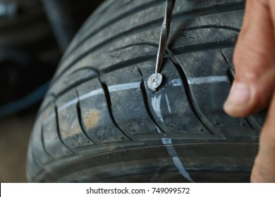 solve problem wheel in garage auto repair shop service. replacement repairman fixing car's tire trying to remove nail from hole. Flat tire. Accident with punctured tires concept.