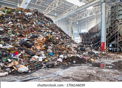 Solving problem of environmental pollution with waste at garbage processing plant - huge pile of garbage prepared for loading to conveyor belt for further sorting and processing with copyspase.