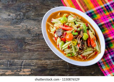 Som Tam (Spicy Papaya Salad) with salted crab, on wooden table ( Thai food)