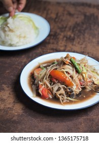 Som Tum Poo - Thai spicy green papaya salad with fermented crabs. Served with steamed sticky rice and vegetable on wooden table.