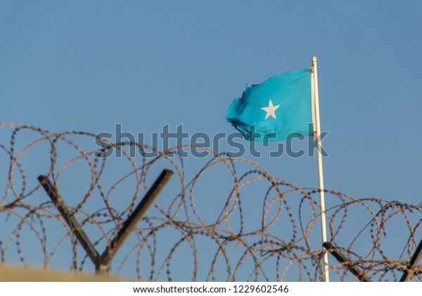 The Somali flag of Somalia, light blue with a five-sided white star, flies on a flag pole above a wall with barbed wire or razor wire in Mogadishu, the capital of Somalia.