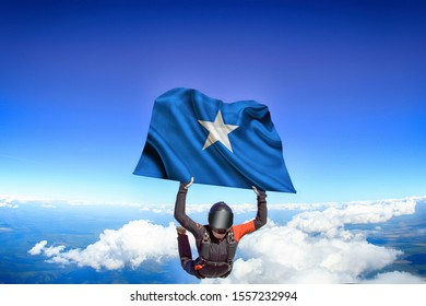 Somalia flag. Flag in skydiving. People in free fall grab flag of Somalia. Patriotism, men and flag.