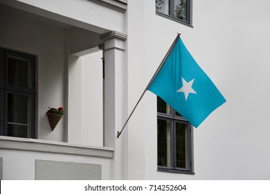 Somalia flag. Somalian flag displaying on a pole in front of the house. National flag of Somalia waving on a home hanging from a pole on a front door of a building.